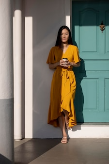 コーヒーを飲みながら街で屋外でポーズをとる美しいアジアの女性の肖像画