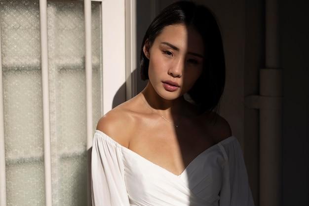 影の中で屋外でポーズをとる美しいアジアの女性の肖像画