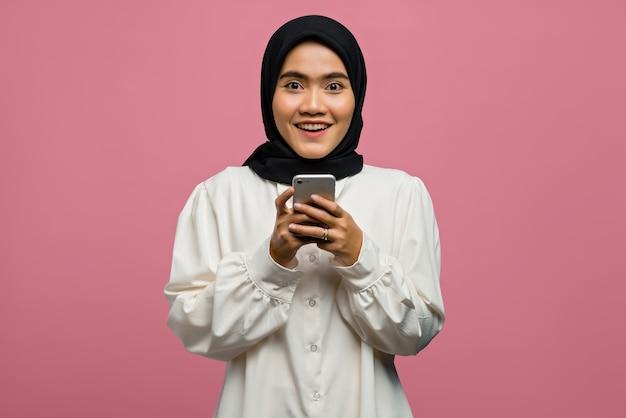 웃 고 스마트 폰 들고 아름 다운 아시아 여자의 초상화