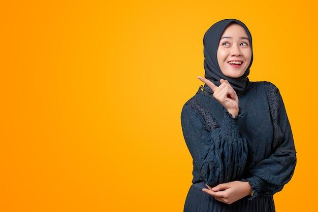笑顔で横を指す美しいアジア女性のポートレート、