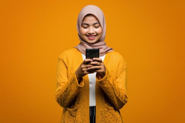 웃 고 스마트 폰을 사용 하여 아름 다운 아시아 여자의 초상화