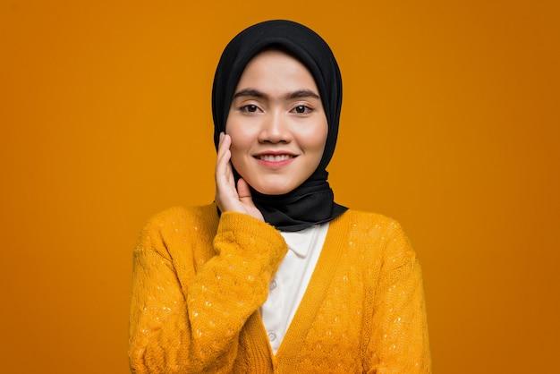 Портрет красивой азиатской женщины, улыбающейся и одетой в желтый кардиган