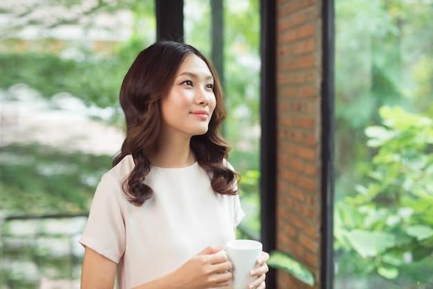 自宅のリビング ルームの窓から見て微笑む美しいアジア女性のポートレート