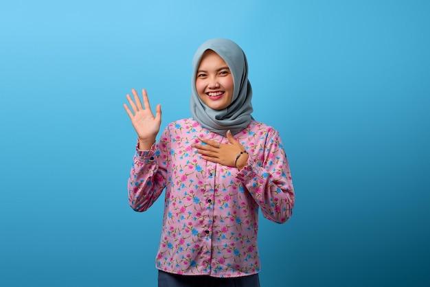 片方の上げられた手ともう一方の心に笑みを浮かべて美しいアジアの女性の肖像画