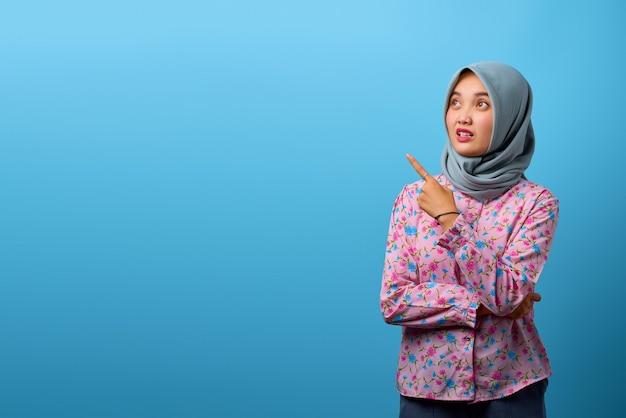 驚いて、青い背景の上のコピースペースを指している美しいアジアの女性の肖像画