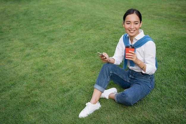 携帯電話を使用して、コーヒーを飲み、公園でリラックスして美しいアジアの女性の肖像画