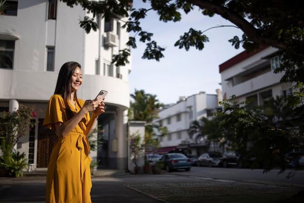 Портрет красивой азиатской женщины, использующей смартфон на открытом воздухе в городе