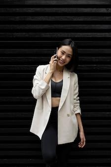 Портрет красивой азиатской женщины, использующей смартфон на открытом воздухе