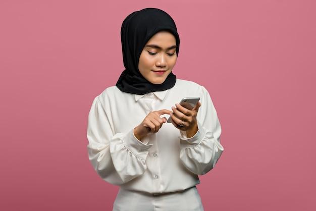 Портрет красивой азиатской женщины в белой рубашке и использующей смартфон