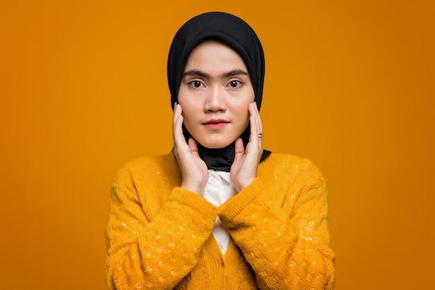 Портрет красивой азиатской женщины в желтом кардигане