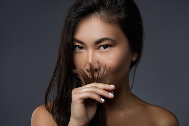 Портрет красивой азиатской женщины с черными здоровыми волосами