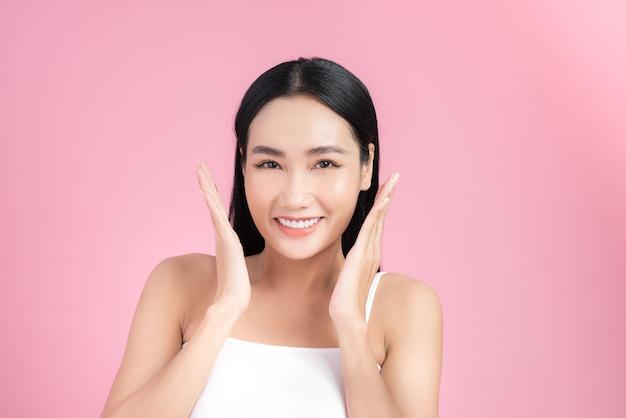 自然なメイクで顔に触れる美しいアジアの女性のポートレート。