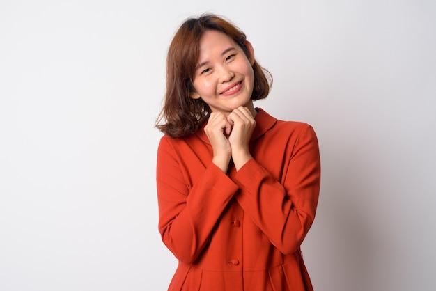흰 벽에 짧은 머리를 가진 아름다운 아시아 여자의 초상화