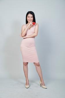 Портрет красивой азиатской молодой женщины, держащей указывая красную форму сердца, изолированную на светло-сером фоне с копией пространства