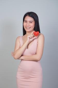 コピースペースと明るい灰色の背景に分離された赤いハートの形を指している美しいアジアの若い女性の肖像画