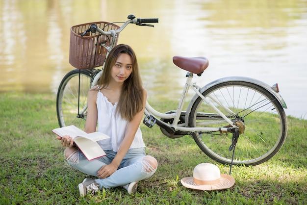 Портрет красивой азиатской молодой женщины прочитал книгу на дворе зеленого цвета сада около велосипеда и пруда.