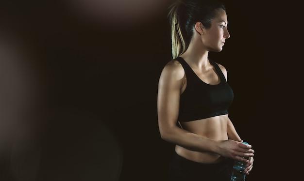 Портрет красивой спортивной блондинки с черным топом, позирующей на темном фоне