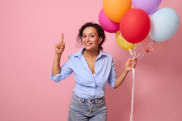 コピースペースと明るいピンク色の背景に人差し指で指している気球を保持している美しい魅力的なかわいい女性の陽気な美しい混血の女性の肖像画