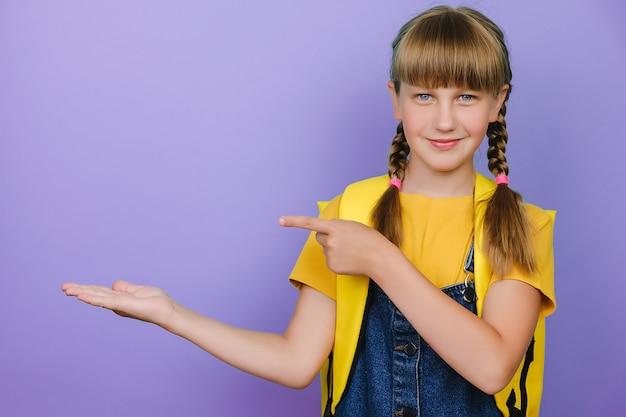 노란색 배낭을 메고 보라색 배경 벽 위에 고립된 포즈를 취하고 손으로 발표하고 손가락으로 가리키는 동안 카메라를 향해 웃고 있는 아름다운 똑똑한 여학생의 초상화
