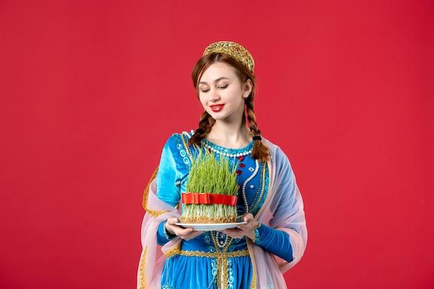 赤でsemeniを保持している伝統的なドレスの美しいアゼルバイジャンの女性の肖像画