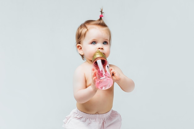Портрет красивой девочки-малыша в подгузнике с розовой бутылкой воды