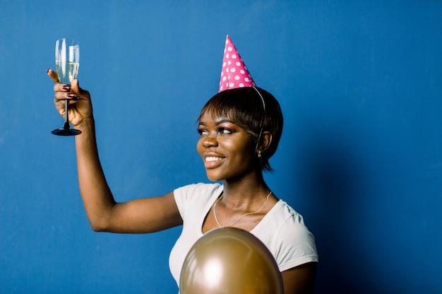 파티에서 쉬고 아름 다운 생일 아프리카 여자의 초상화. 푸른 공간에 포즈 샴페인과 공기 풍선 유리를 들고 꽤 웃는 아프리카 소녀