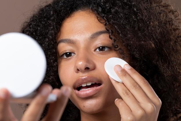 그녀의 피부 관리 일과를 하는 아름다운 흑인 여성의 초상화