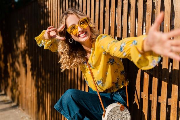 Портрет красивой блондинки, эмоционально смеющейся, стильной улыбающейся женщины в желтой блузке в солнцезащитных очках, соломенной сумочке в балийском стиле