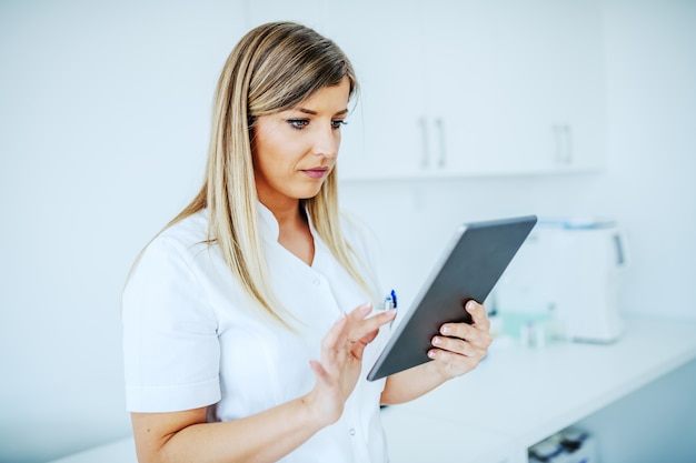 実験室に立っている間タブレットを使用して白い制服を着た美しい金髪女性ラボアシスタントの肖像画。