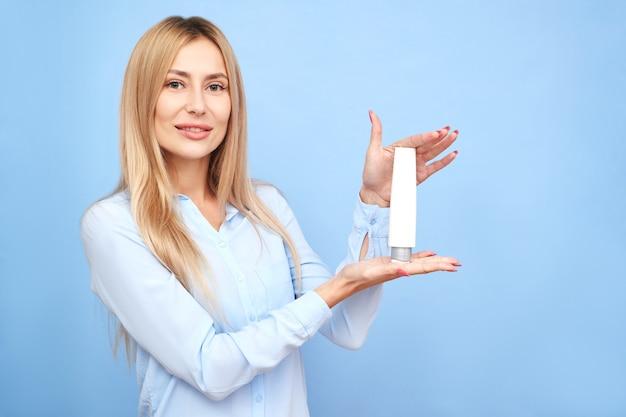 Портрет красивой белокурой девушки демонстрирует продукт, держащий бутылку, изолированную на синем фоне