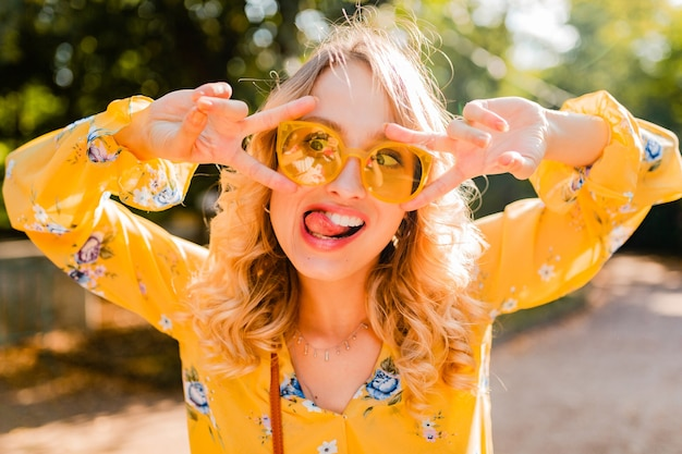 サングラス、面白いクレイジーな顔の表情を身に着けている黄色いブラウスで美しい金髪のスタイリッシュな感情的な女性の肖像画
