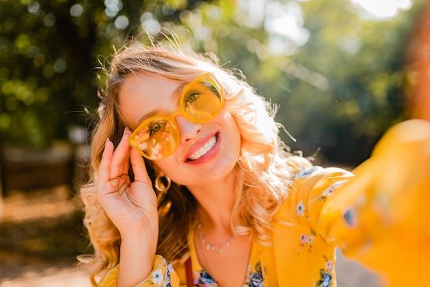 Портрет красивой блондинки стильной улыбающейся женщины в желтой блузке в солнцезащитных очках, делающей селфи фото