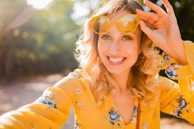 自撮り写真を作るサングラスを身に着けている黄色いブラウスで美しい金髪のスタイリッシュな笑顔の女性の肖像画