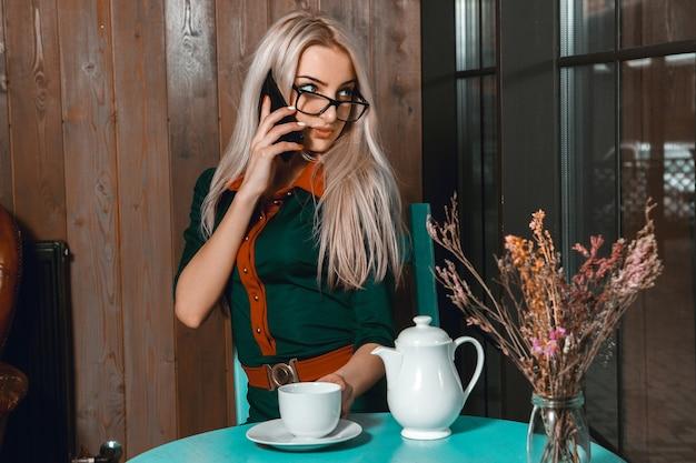 전화 통화 하 고 도시 카페에서 창에서 멀리보고 아름 다운 금발 여자의 초상화.