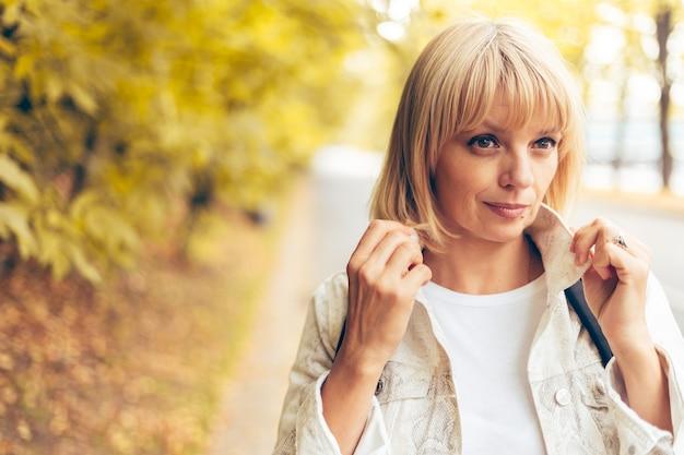 Портрет красивой блондинки взрослой женщины в осеннем парке на природе прогулки на открытом воздухе