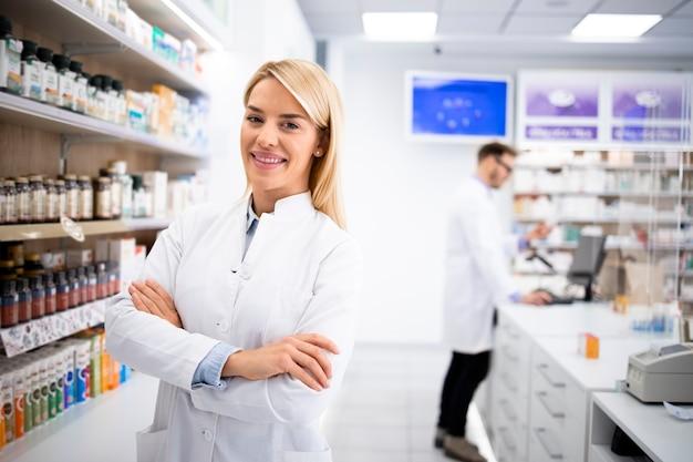 薬と棚のそばの薬局に立っている美しい金髪の女性薬剤師の肖像画。