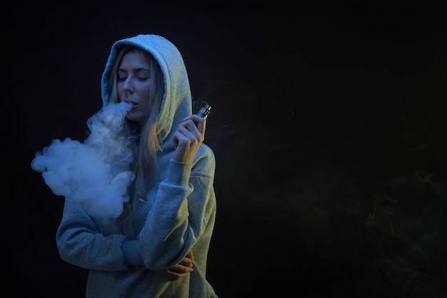 Портрет красивой блондинки в серой толстовке с капюшоном курит вейп на черном фоне студии, облако парового дыма, мини-кальян