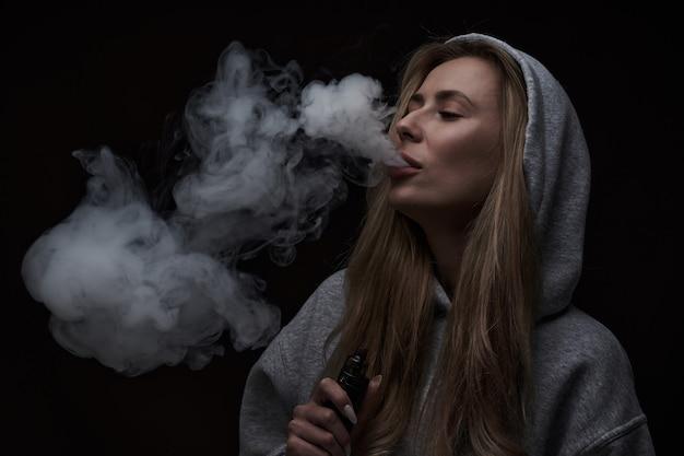 Портрет красивой блондинки в серой толстовке с капюшоном курит вейп на черном студийном фоне, облако парового дыма, мини-кальян