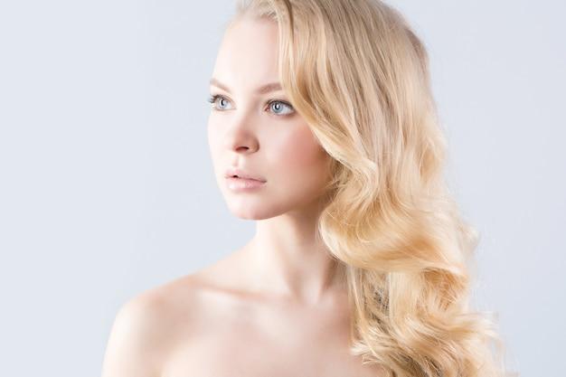 美しいブロンドの豊かな髪のカーリングの肖像画。美容と健康。
