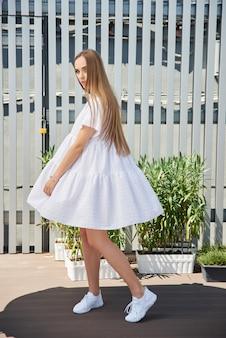Портрет красивой белокурой модели в летнем белом платье. девушка позирует на крыше дома.