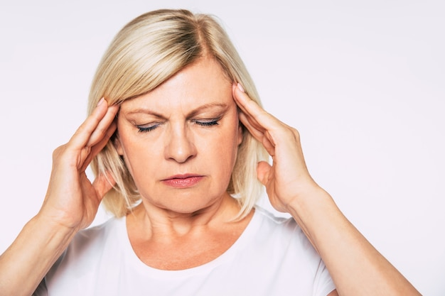 눈을 감고 머리에 손을 얹고 있는 동안 심한 두통을 가진 아름다운 금발 노부인의 초상화