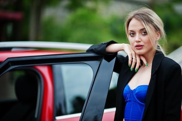 赤い都市の車の近くの明るいメイクですべて黒の美しい金髪のセクシーなファッション女性モデルの肖像画。