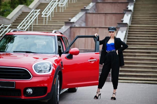赤い都市の車の近くに明るいメイクで、キャップとすべての黒、青のコルセットで美しい金髪のセクシーなファッションの女性モデルの肖像画。