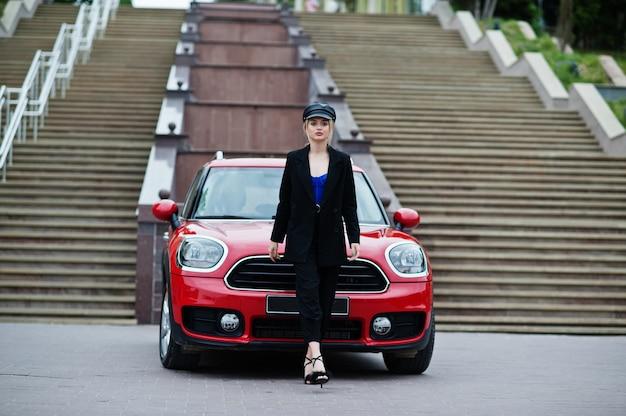 赤い都市の車の近くに明るいメイクでキャップとすべて黒の美しい金髪のセクシーなファッション女性モデルの肖像画。