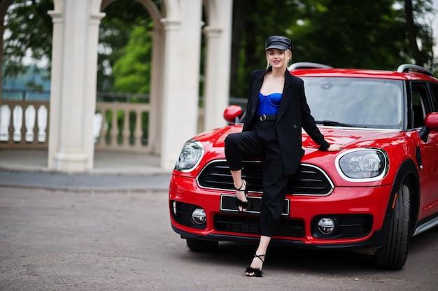 キャップと明るいメイクですべて黒の美しい金髪のセクシーなファッション女性モデルの肖像画は、赤い都市の車のフードに座っています。
