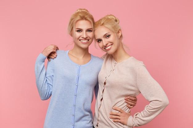 異なる色の同じカーディガンで、お互いに抱き合ってポーズをとって、幸せで面白い、美しい金髪の双子の姉妹の肖像画は、ピンクの背景の上に広く笑っています。
