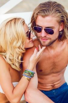 아름다운 금발의 여자와 잘 생긴 남자의 초상화, 해변에서 세련된 선글라스를 착용