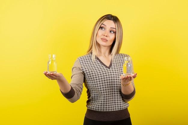 Портрет красивой блондинки, держащей два стакана негазированной воды.