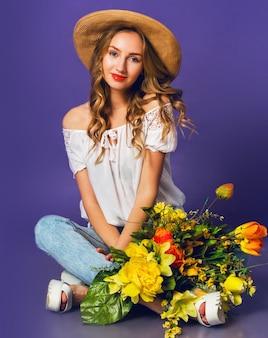 紫色の壁の背景の近くのカラフルな春の花の花束を保持しているスタイリッシュな麦わら夏帽子の美しい金髪の若い女性の肖像画。