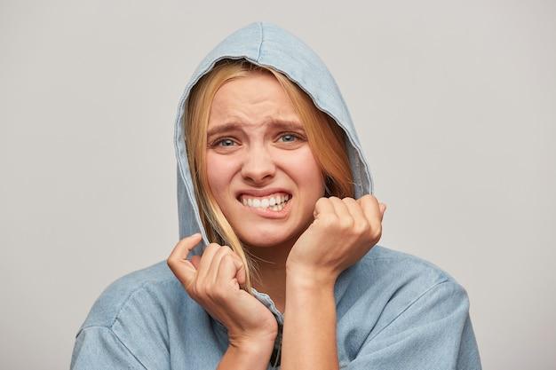 Портрет красивой блондинки молодой женщины, руки держат капюшон, выглядит расстроенным и немного напуганным